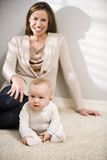 Mother sitting on floor with six month old baby. Mother sitting on floor at home with six month old baby Stock Photography