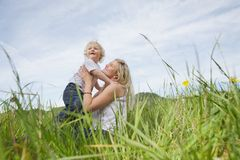 Mother sitting on grass while playing with boy Royalty Free Stock Photo