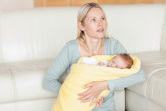 Mother sitting with her baby in front of the couch Royalty Free Stock Images