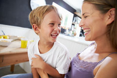 Mother Sitting With Laughing Son At Breakfast Table Stock Photos
