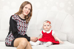 Mother sitting near baby girl on white sofa Royalty Free Stock Images