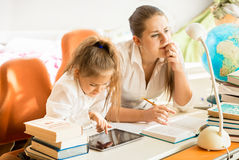 Mother sitting next to daughter doing homework Royalty Free Stock Photo