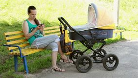 Mother sitting in the park rolls the stroller and looking at smartphone stock video