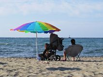 Mother Sitting and Relaxing in Chair on Sandy Beach Next to Baby Carriage Stroller Protected from Sun by Colorful Parasol Umbrella stock photography