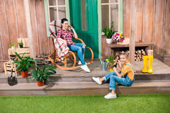 Mother sitting in rocking chair and smiling daughter cultivating plant on porch. Happy mother sitting in rocking chair and smiling daughter cultivating plant on Royalty Free Stock Image