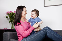 A mother sitting on a sofa holding her baby son Royalty Free Stock Image