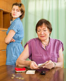 Mother sitting at the table and counting money Stock Photography