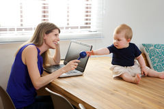Mother sitting at table with laptop and playing with baby boy. Royalty Free Stock Images