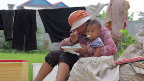 Mother sitting top of garbage bag feeding baby in slums stock footage