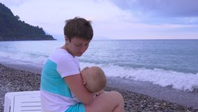 Mother and sleeping baby on the beach stock footage