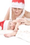 Mother and sleeping baby wearing christmas hut Stock Photography