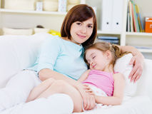 Mother with sleeping daughter at home Stock Image