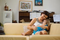 Mother and sleepy child. Smiling women hugging her sleepy little daughter stock photography