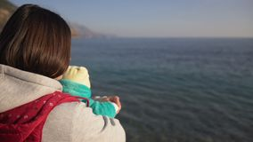 Mother with small baby in her hands stay on beach. Back view. She shows him the sea and gently holds his hand stock footage