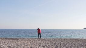 Mother with small baby in her hands stay on beach. Back view stock footage