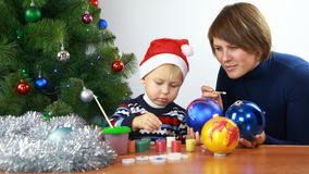 Mother with small boy paint christmas balls Royalty Free Stock Photo