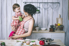Mother and small child in the kitchen at home beautiful and happy royalty free stock photos