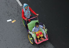 A mother with a small child riding a rickshaw in solo car free d Stock Image