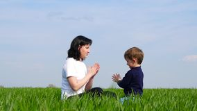 Mother and small child sit on the green grass and play, slapping each other`s hands. The concept of happy family, care