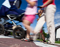 Mother with small children and a pram crossing a street. (motion blurred image Royalty Free Stock Photography