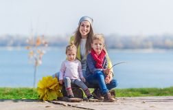 Mother with the small children sits on the river bank in the autumn park royalty free stock photo