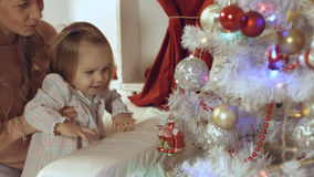 Mother with a small daughter decorate a festive Christmas tree Stock Image