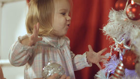 Mother with a small daughter decorate a festive Christmas tree Royalty Free Stock Images