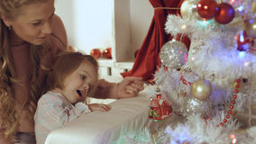Mother with a small daughter decorate a festive Christmas tree Royalty Free Stock Photo