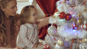 Mother with a small daughter decorate a festive Christmas tree Stock Photography