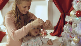 Mother with a small daughter decorate a festive Christmas tree Royalty Free Stock Photos