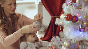 Mother with a small daughter decorate a festive Christmas tree Stock Photo