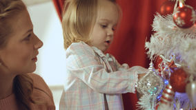 Mother with a small daughter decorate a festive Christmas tree Royalty Free Stock Image
