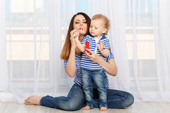 Mother and small daughter inflate soap bubbles Stock Images