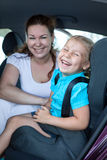 Mother with small daughter laughing on back seat of car Stock Photography