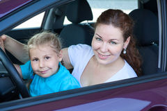 Mother with small daughter sitting together on driver seat Royalty Free Stock Images