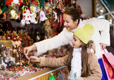 Mother with small daughter staring at counter of Christmas marke Royalty Free Stock Photos