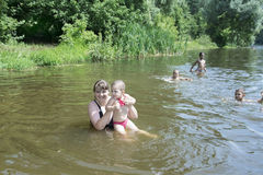 Mother with a small daughter swimming in the river. Stock Photos