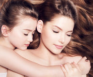Mother with a small daughter 8 years lying together with closed. Beautiful young mother with a small daughter 8 years lying together with closed eyes royalty free stock image