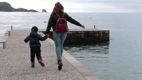 Mother And Small Son On The Pier. Slow Motion - Rear View - An Unidentified Mother And Small Son In Casual Clothes And With Backpacks Running Down The Pier To stock footage