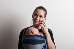 Mother with smartphone and baby sleeping in sling. Studio shot. Royalty Free Stock Photo