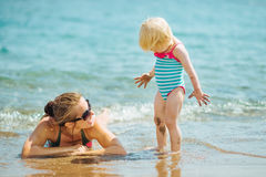 Mother and smeared with mud baby on sea beach Royalty Free Stock Photos