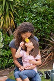 Mother smelling a flower with her daughter Royalty Free Stock Image