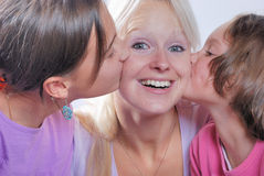 A mother smiles as she receives a kiss Royalty Free Stock Photo