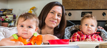 Mother Smiles With Babies. A mother in the kitchen poses with babies stock photos