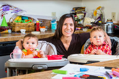 Mother Smiles With Babies. Smiling mother poses with her babies royalty free stock photo