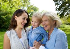 Mother smiling with baby and grandmother. Close up portrait of a mother smiling with baby and grandmother stock images