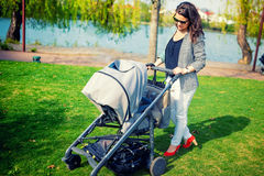 Mother smiling with baby in park. Mother walking child with pram or baby stroller Royalty Free Stock Image