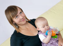 Mother smiling and baby playing. Happy mother sitting with baby on sofa. Baby is playing with toy stock photography
