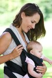 Mother smiling with baby in sling Stock Photography