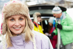 Mother Smiling At Camera Whilst Family Load Skis Royalty Free Stock Photo